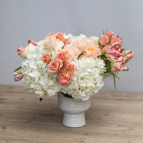 An image of a light pink rose and white hydrangea floral arrangement