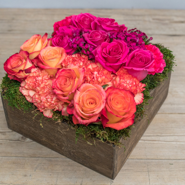 An image of pink and orange pink roses in a wood box planted arrangement for Mother's Day