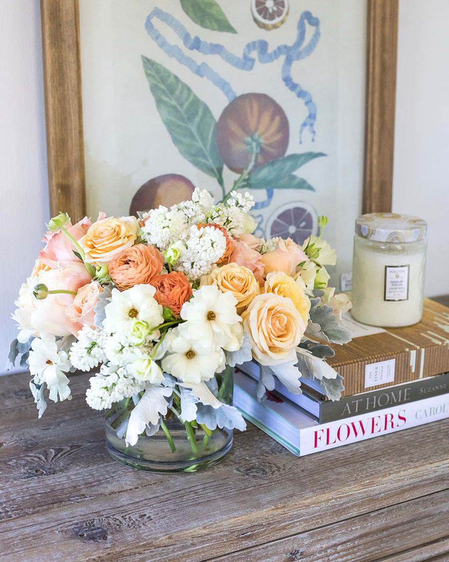 An image of a white and orange floral arrangement for Mother's Day