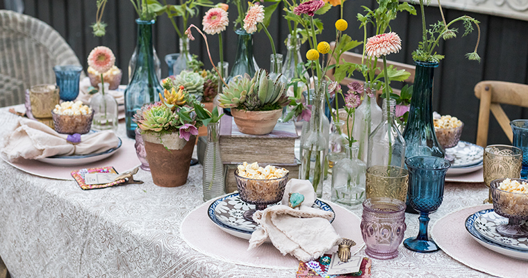 An image of a purple, blue and light pink glasses and dishes dining set up surrounded by dahlias and succulents