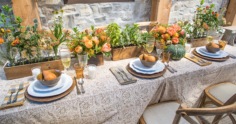 An image of a fall table that is set with a cream color tablecloth, rattan placemats, flowers in shades of oranges and herbs and pears.
