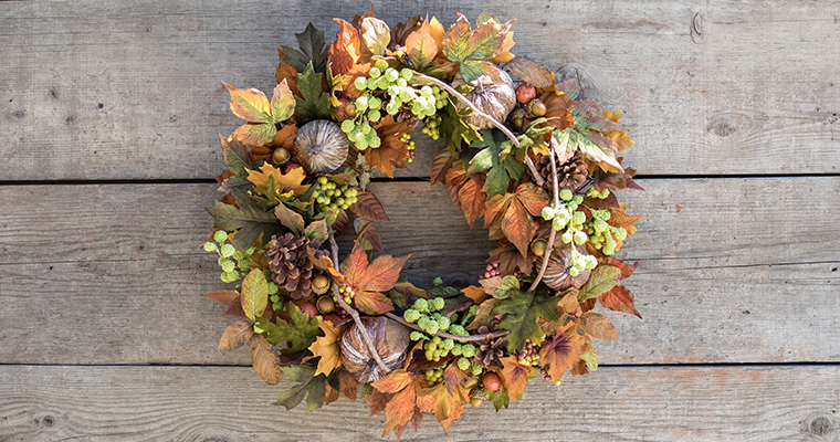 An image of a fall floral wreath with persimmons, fall leaves, hops, and grapevine