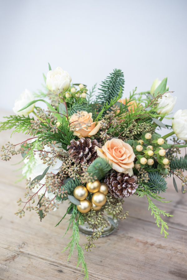 An image of orange roses with golden ball ornaments and pinecones arrangement