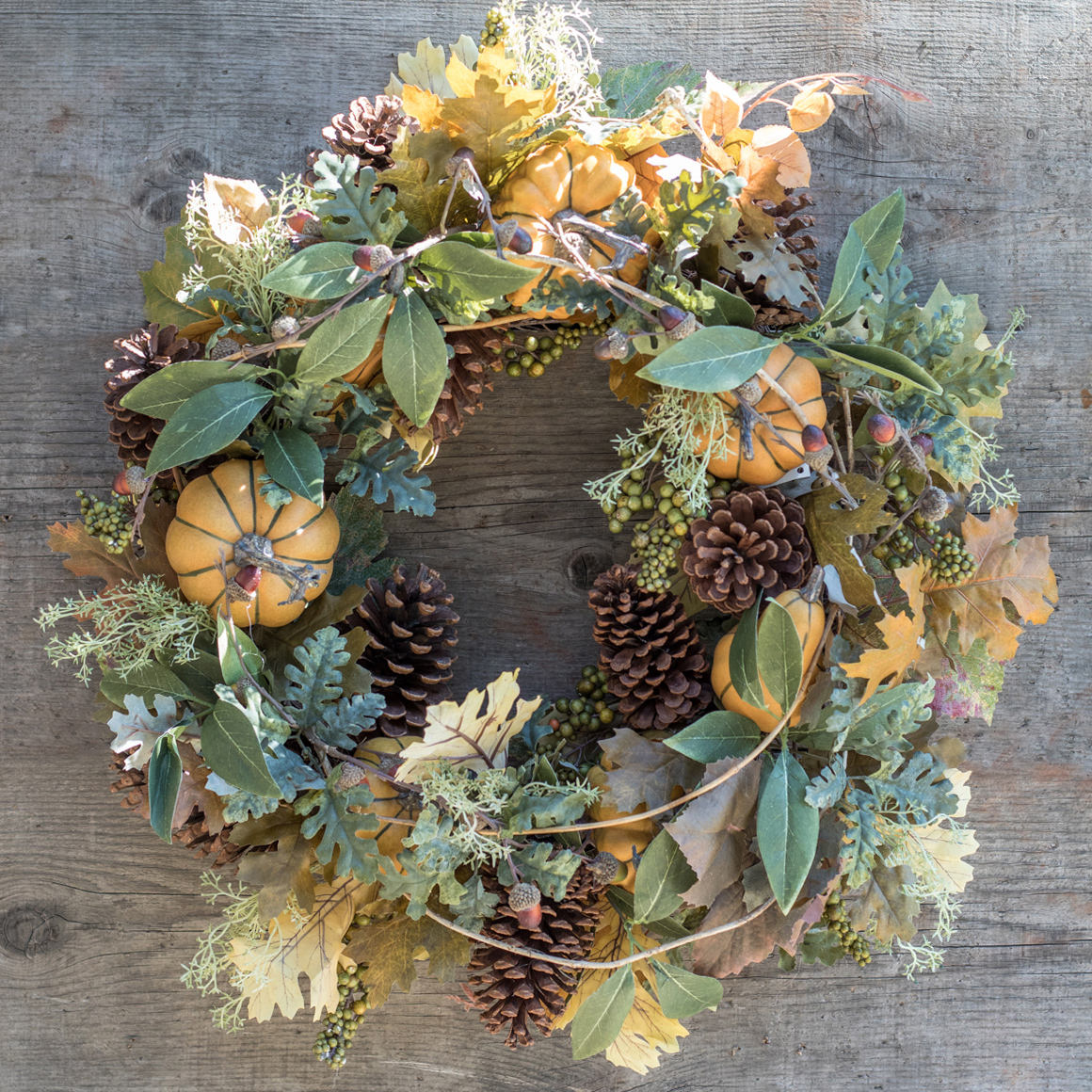 An image of a pumpkin pinecone wreath