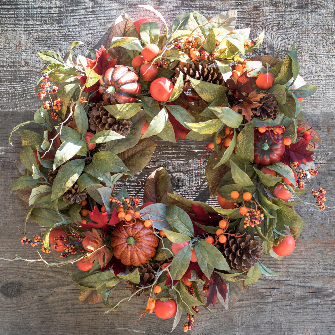 An image of a fall wreath containing pumpkins, pinecones and berries