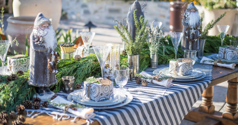 An image of a modern rustic christmas table setting with fresh greenery, glassware, and silver accents