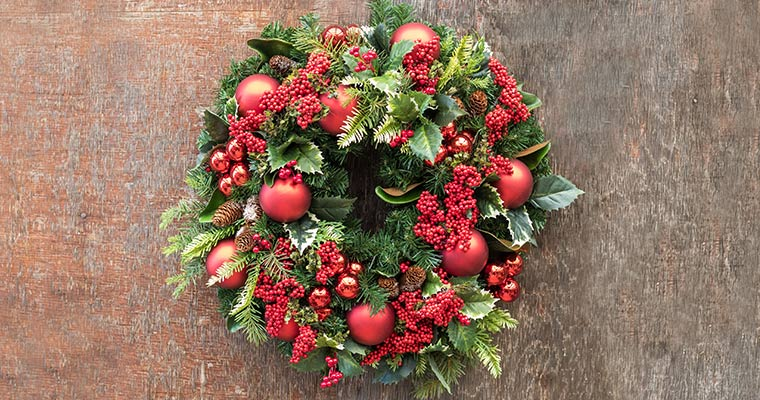 An image of red ball ornaments, red berries and pinecones