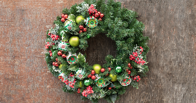 An image of a wreath with red, green, white ornaments and red berries