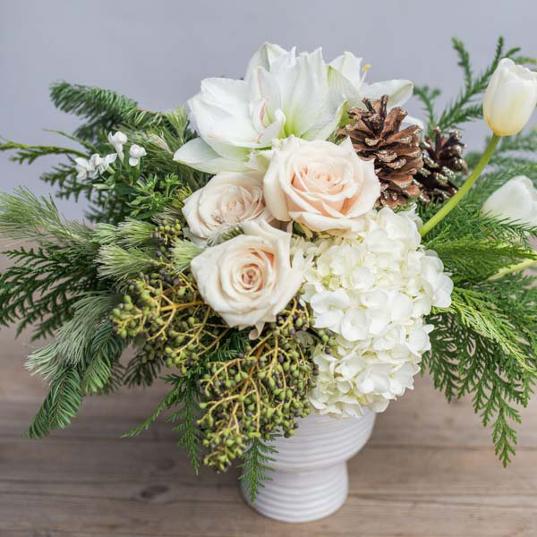 An image of a floral arrangement with light orange rose, white hydrangea and pinecone