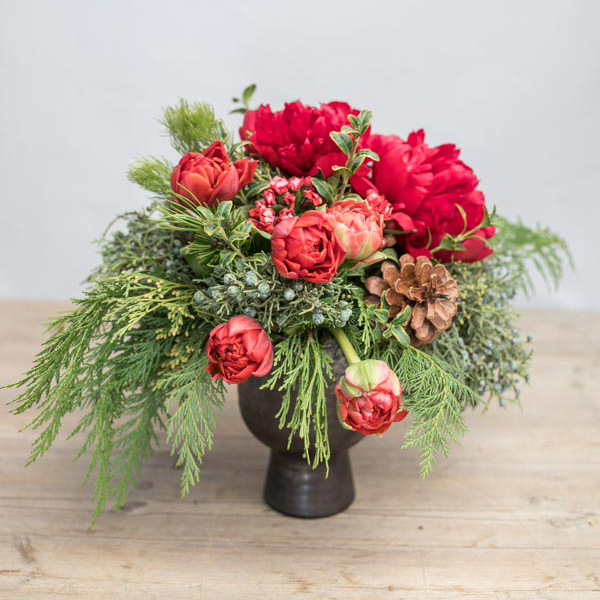 An image of red dahlias and pinecones Christmas arrangement