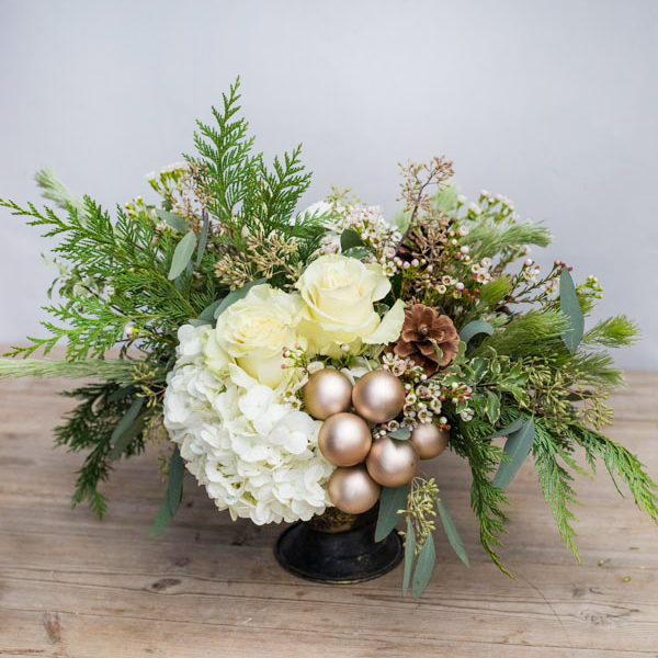 An image of white roses and hydrangeas and rose golden ball ornaments floral arrangement