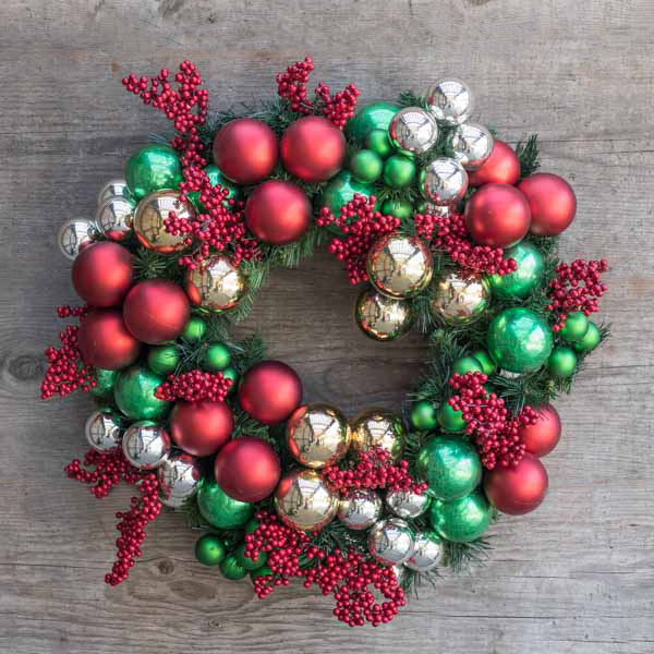 An image of red, green and gold ball ornament with red berries decoratedwreath