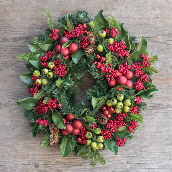 An image of a red ball ornament with red berries and pinecones wreath