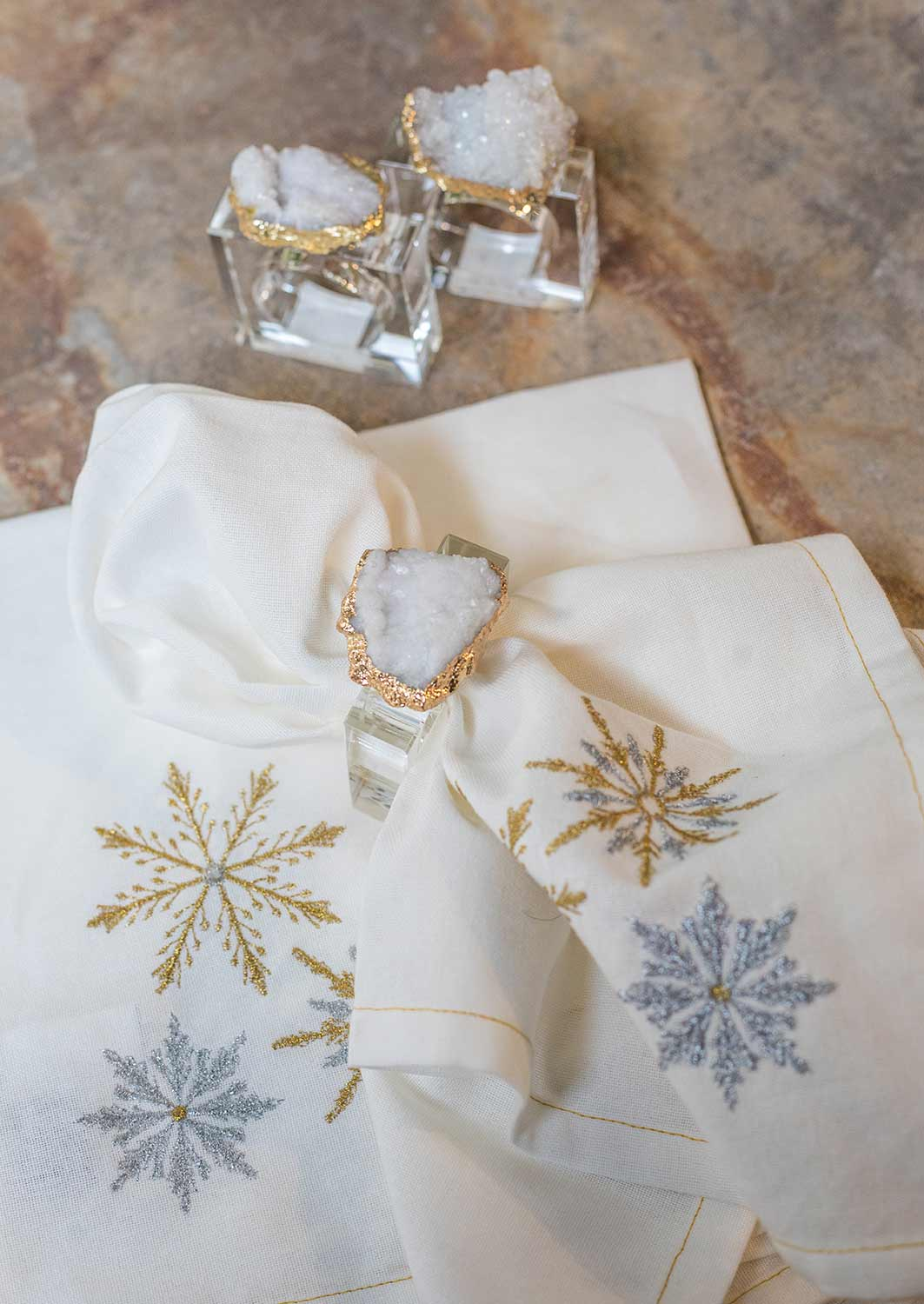 An image of a silver and gold snowflake white Christmas napkins with a white quartz napkin rings