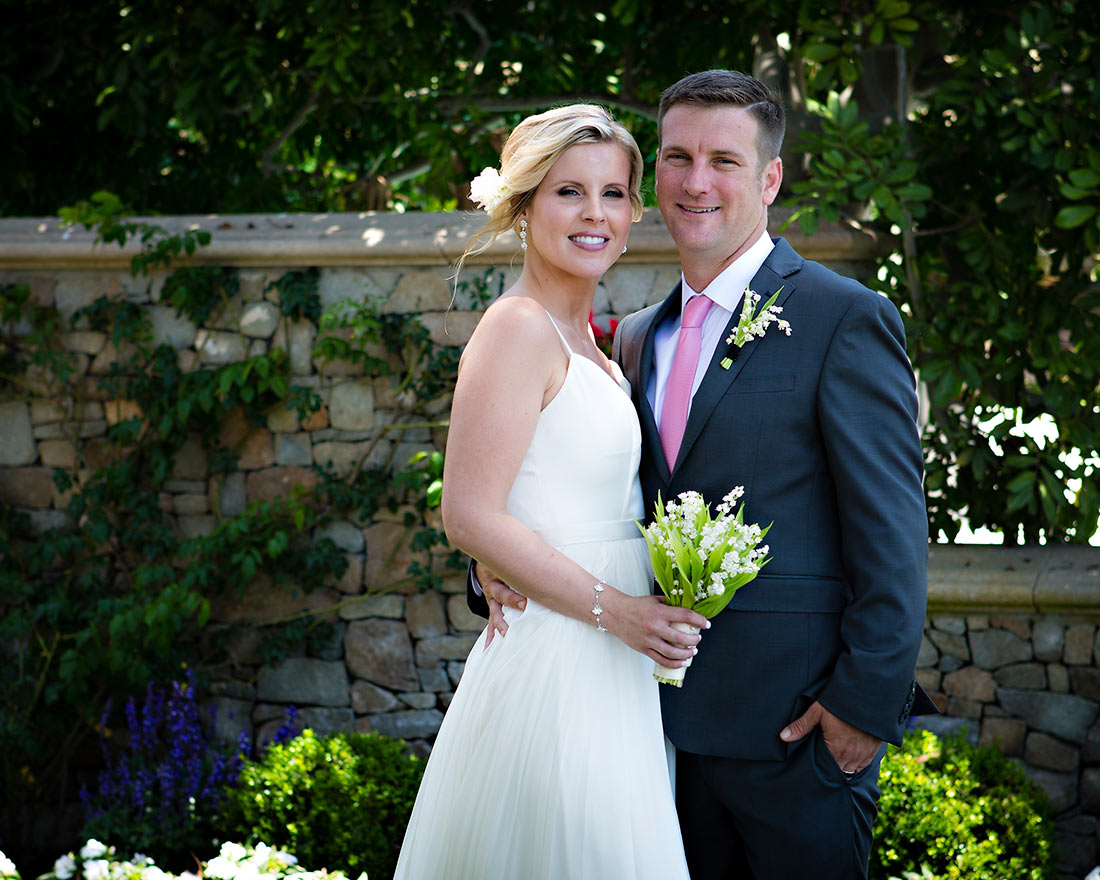 An image of Mr. and Mrs. Dunzer who is holding a simple little white flowered bouquet
