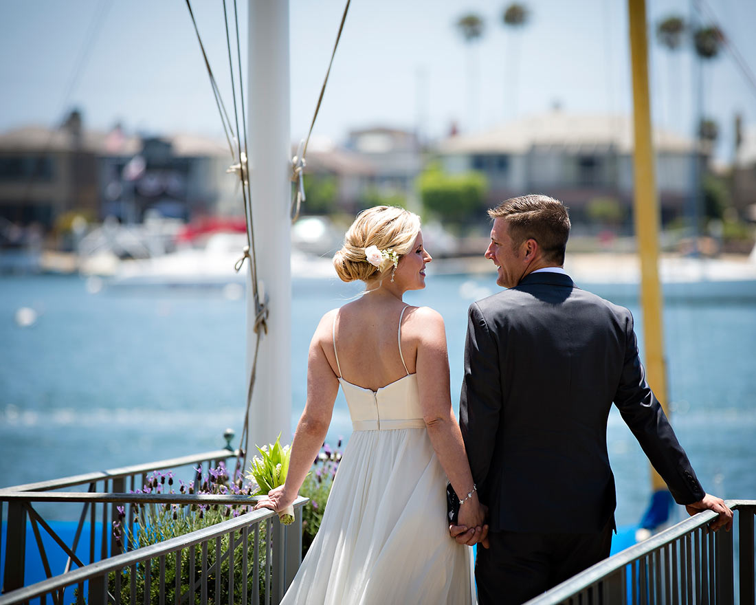 An image of the backs of the bride and groom in front of the harbor