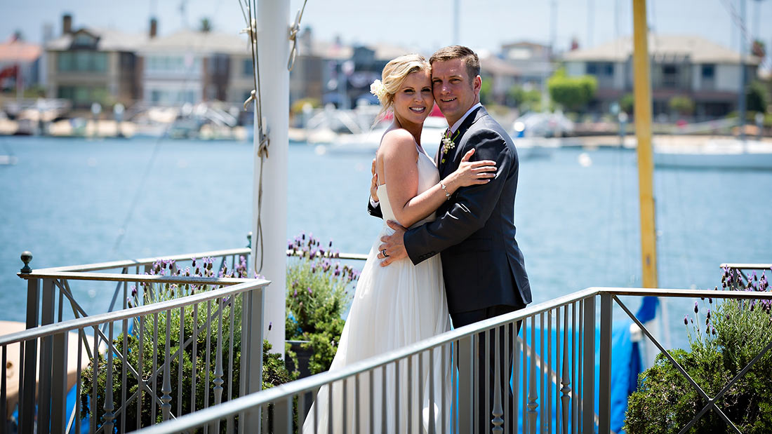 An image of the bride and groom Dunzer posing in front of the harbor