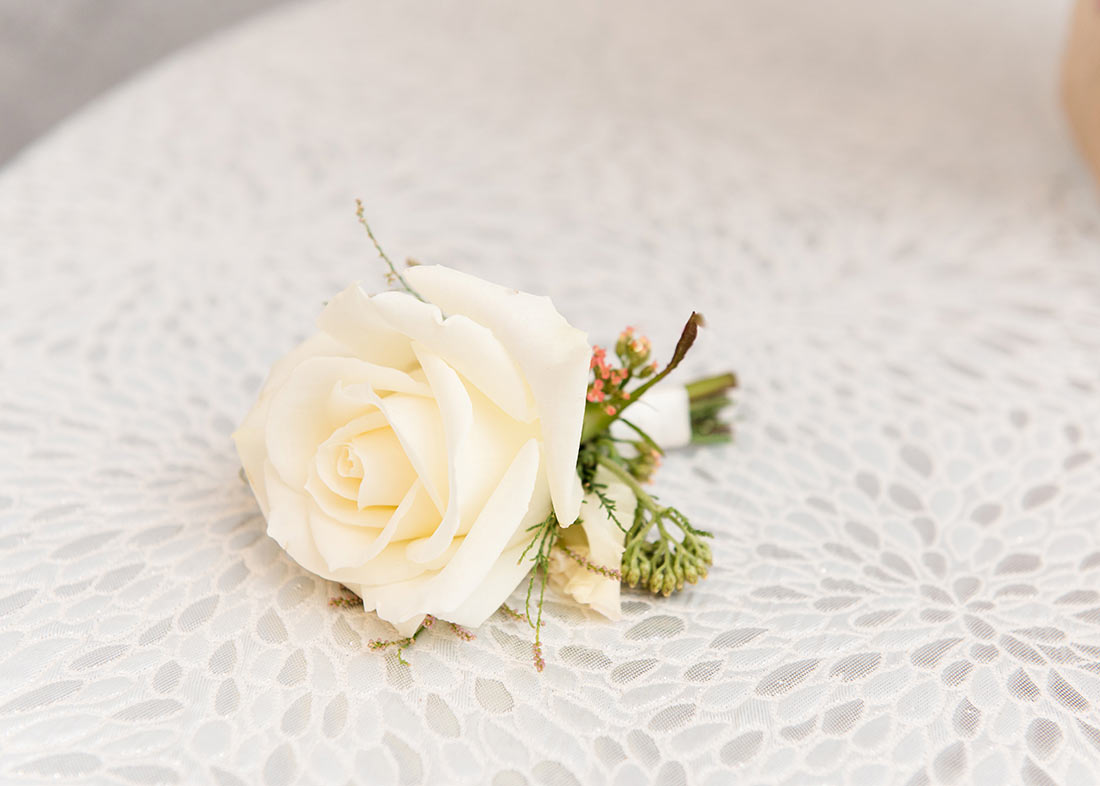 An image of a single white rose corsage laying down on white lace