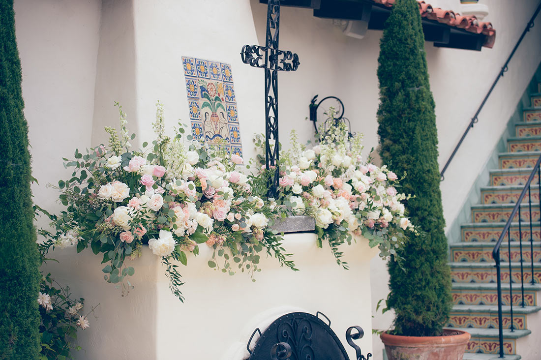 An image of the white and light pink roses decorated around an iron cross sitting on the mantle of the fireplace for the Herbert Wedding