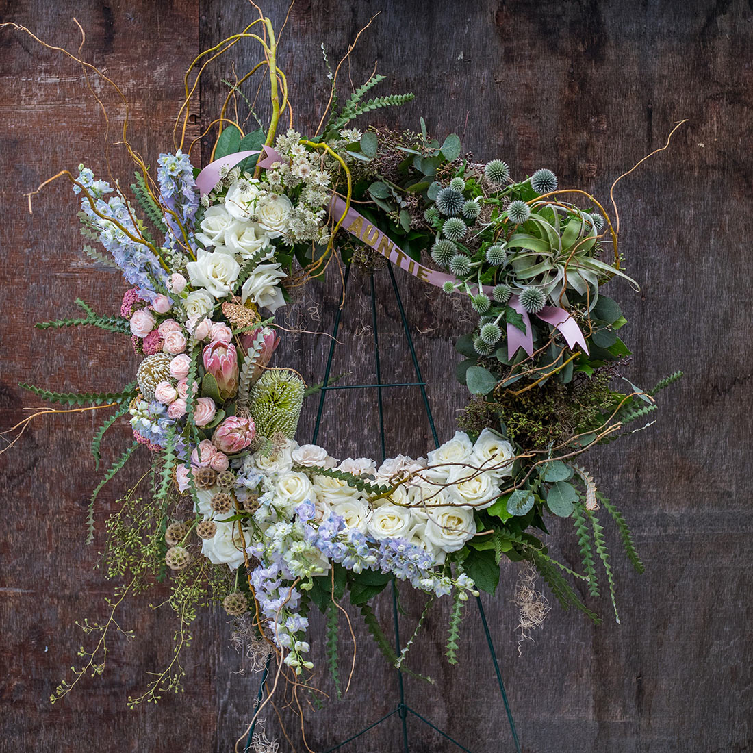 An image of a white and pink rose floral funeral wreath