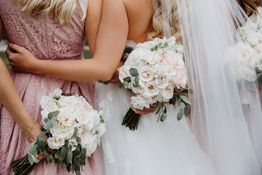 An image of a bride and bridesmaid holding white rose bouquets