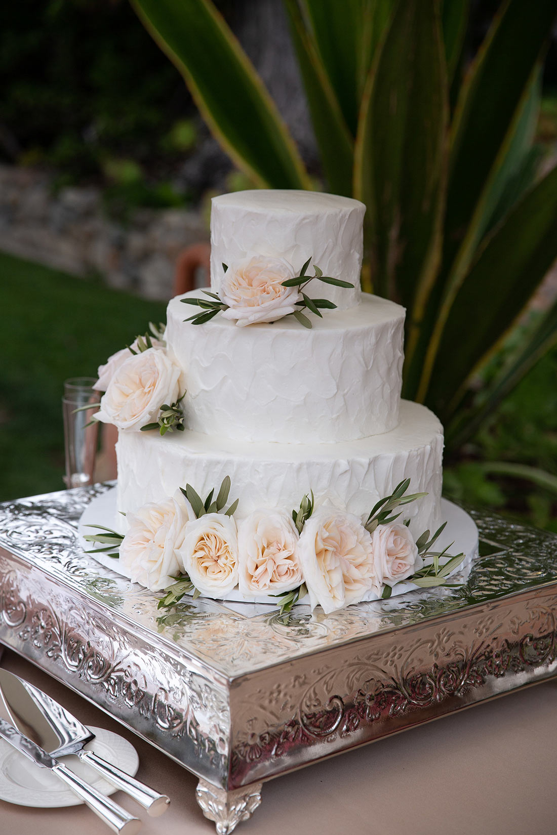 An image of a wedding cake decorated with white frosting and light orange roses