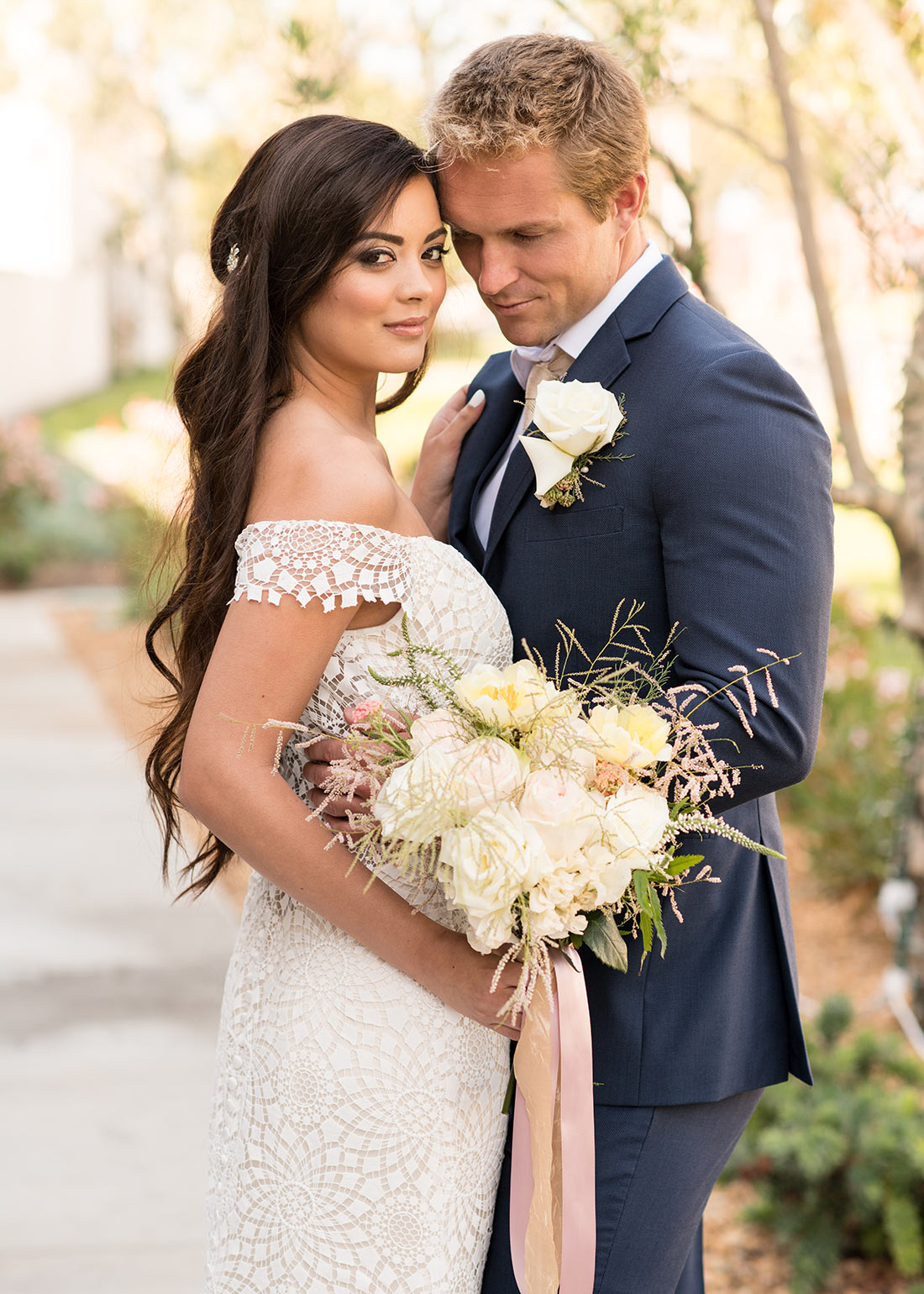 An image of a groom and bride who is holding a white rose bouquet