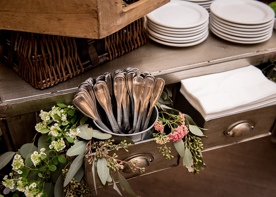 An image of metal drawers decorated with pink and white tiny flowers surrounding silverware