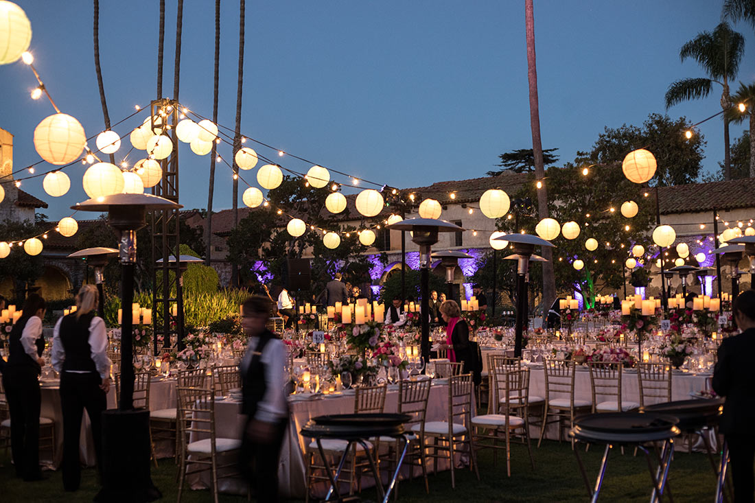 An image of the hanging light decorations over the decorated candle and floral tables at the Mission San Juan Capistrano Gala