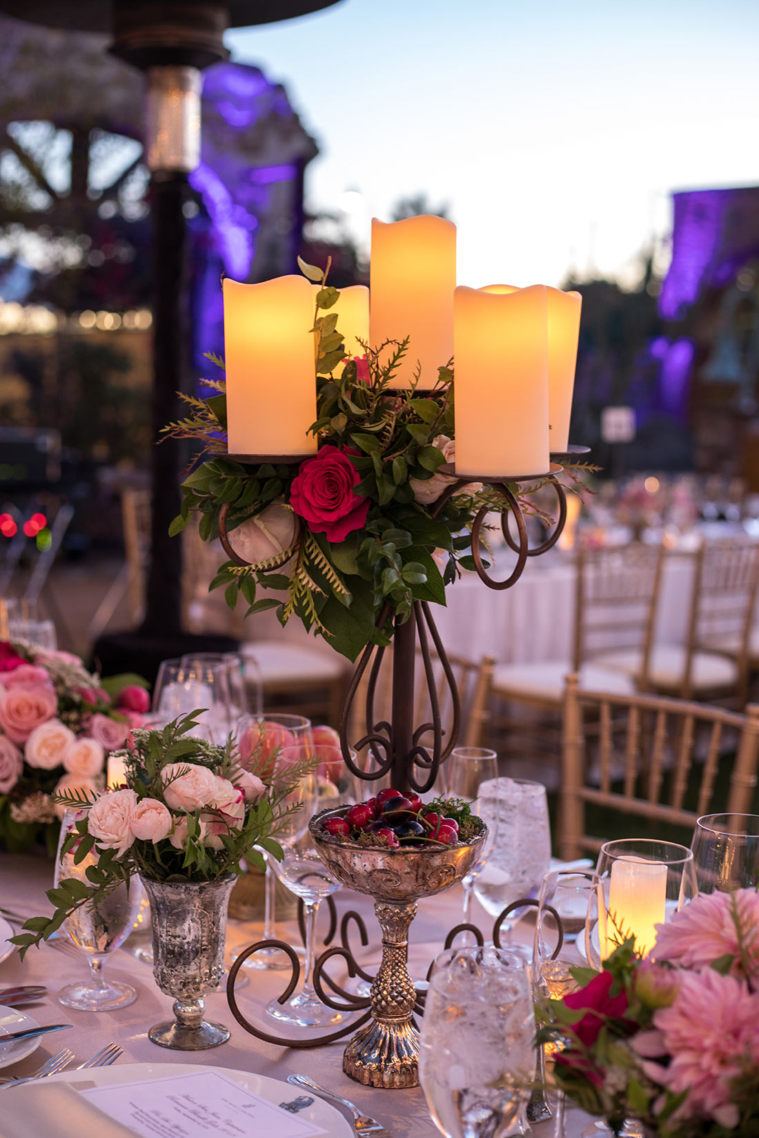An image of the dining piece set with candles and red roses at the Mission San Juan Capistrano Gala