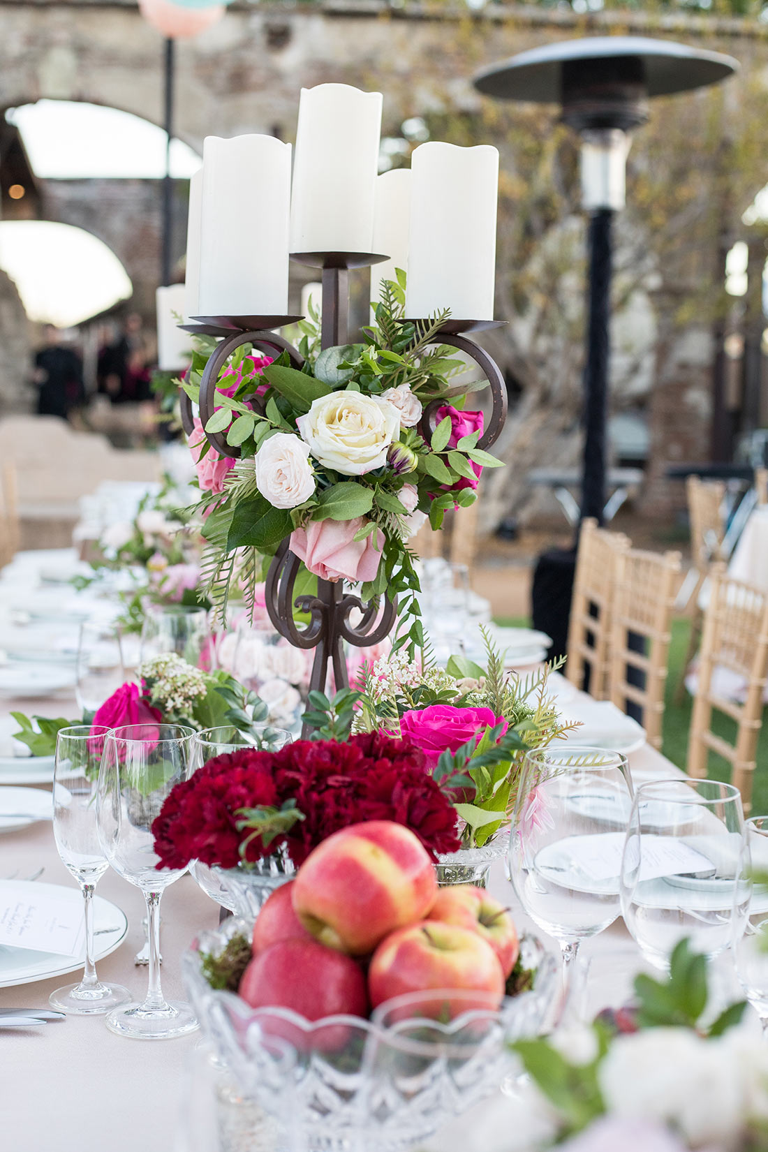 An image of the center piece of candles decorated with white, light pink and pink roses for the Mission San Juan Capistrano Gala