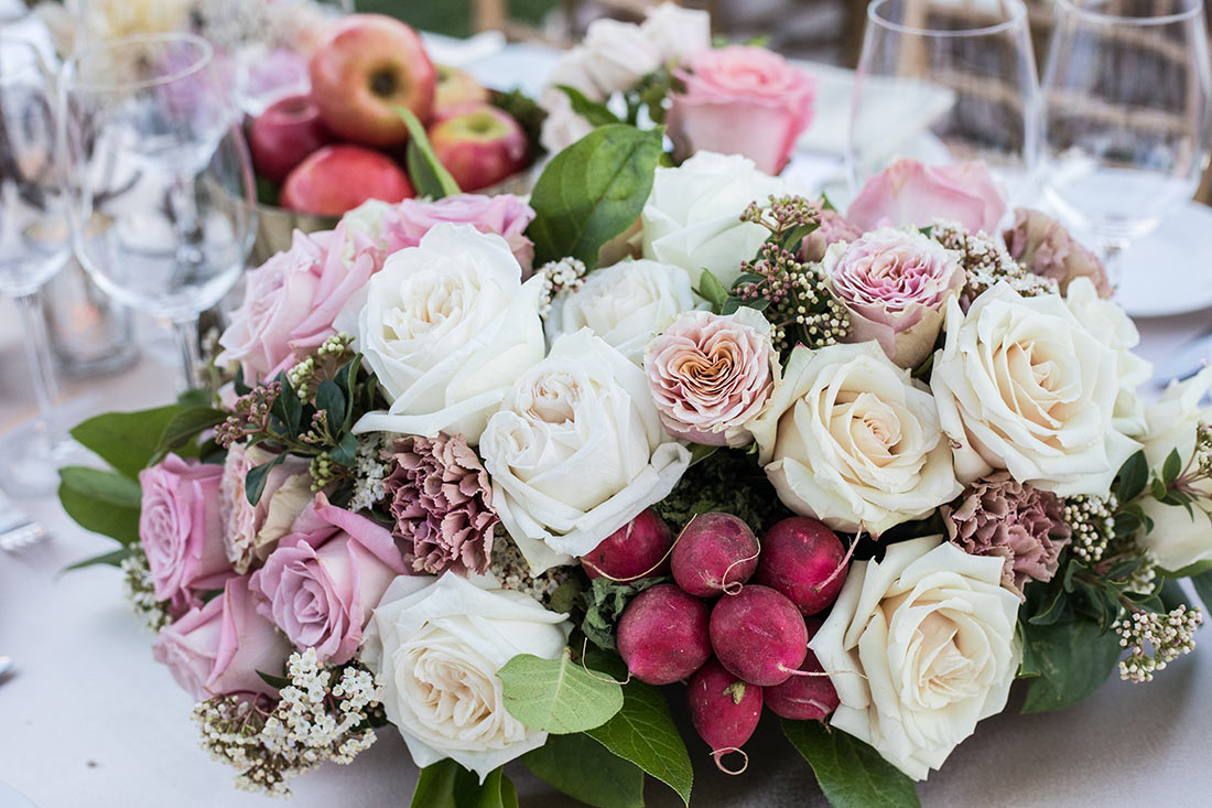 An image of a floral arrangement consisting pink, white and light purple roses along with radishes for the Mission San Juan Capistrano Gala