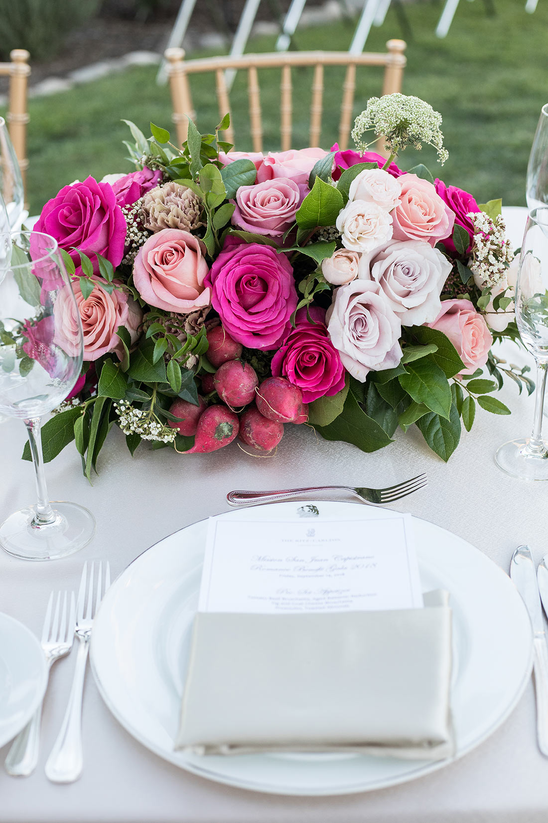 An image of the plate set up with the light pink, white and pink rose floral for the Mission Juan Capistrano Gala