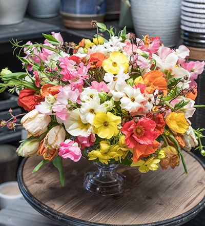 An image of a orange, white, yellow and pink poppy floral arrangement
