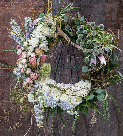 An image of white, light pink and light blue flowers celebration of life wreath