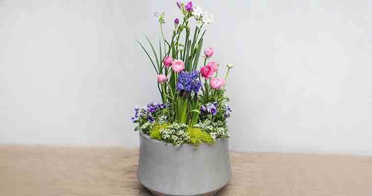 An image of an arrangement of pink and purple flowers in a pot container workshop