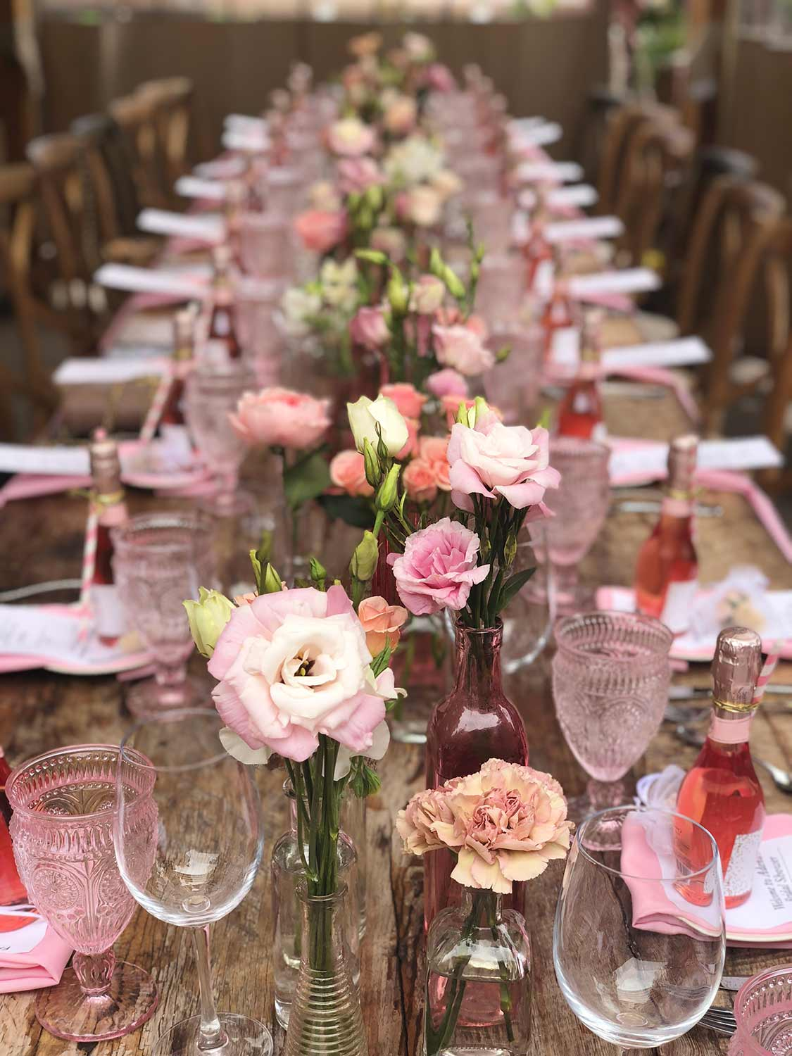 An image of a dinner table with pink glasses, small rosa bottles and pink roses in pink vases