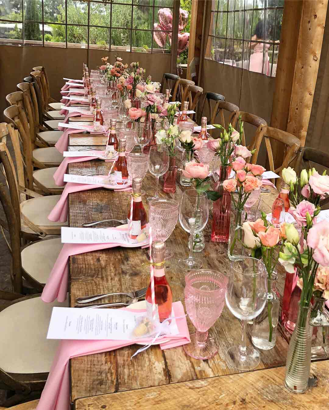 An image of a dining set up of pink napkins, pink glasses, a small rosa bottle and pink roses in pink vases