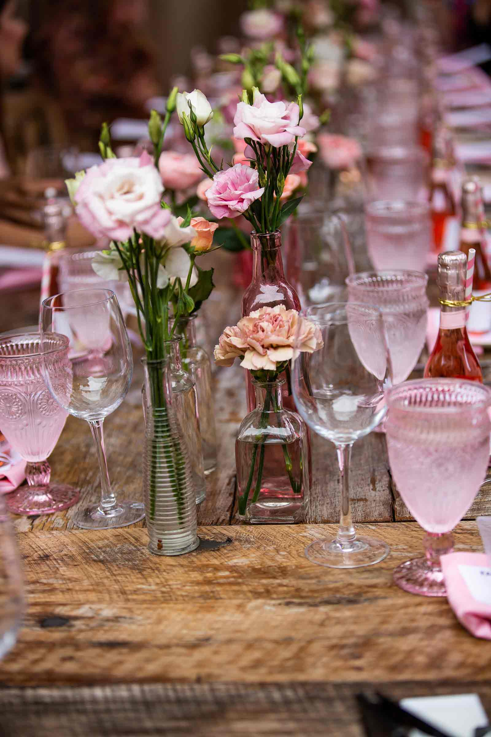 An image of pink roses surrounded by pink glasses