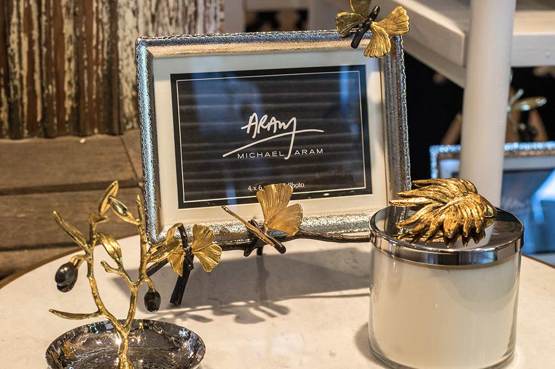 An image of a silver frame and candle topped with gold leaves or butterflies from the Michael Aram Collection