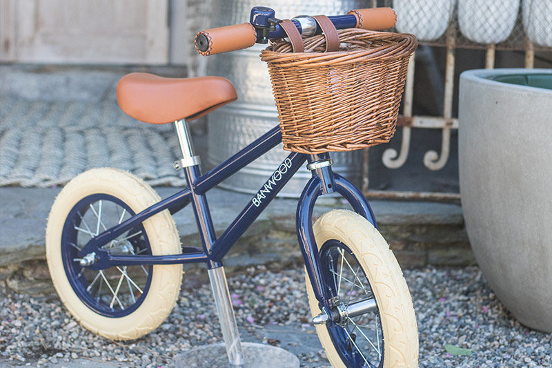 An image of a navy blue balance bike with basket