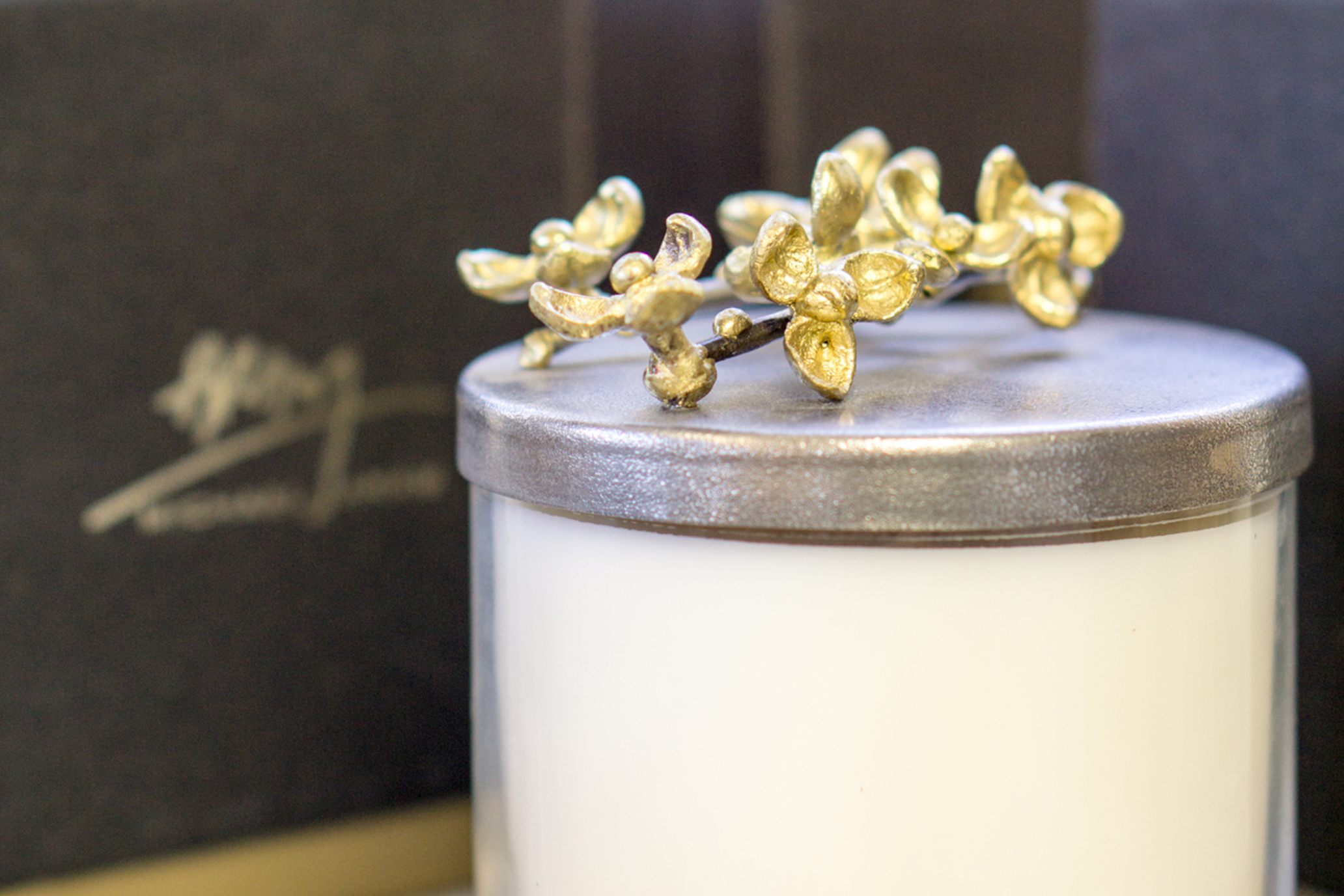 An image of a Michael Aram candle with gold orchid topper