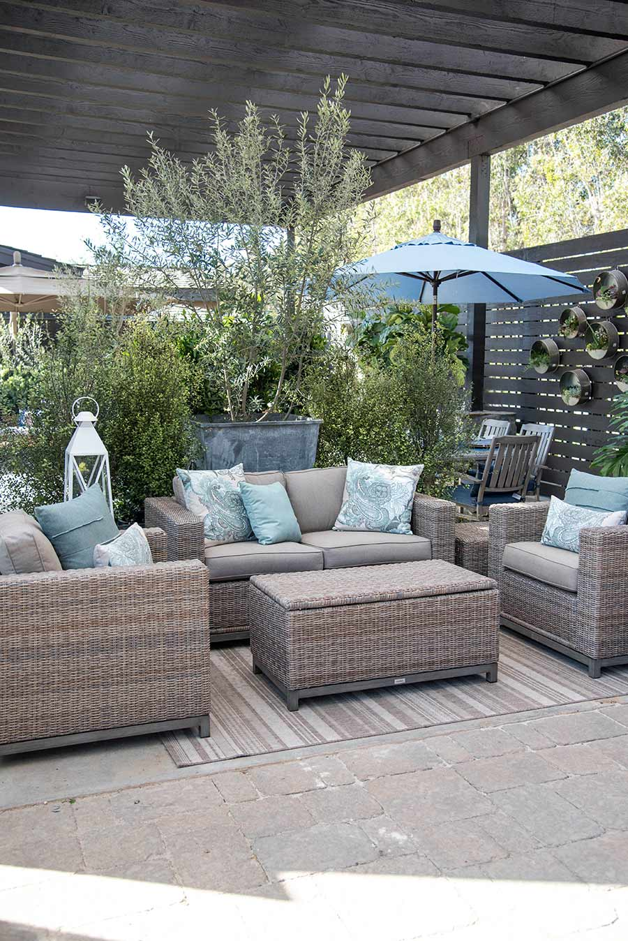 A side view of the Skycrest Loveseat Outdoor Set with white and green pillows