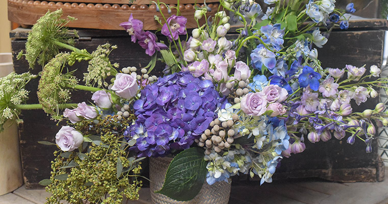 An image of a floral arrangements with blue, light blue, violet, and light purple flowers for Floral Workshop