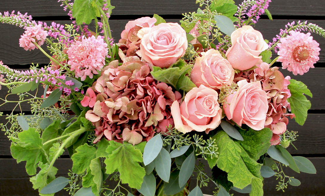 An image of a light pink rose and hydrangea floral arrangement